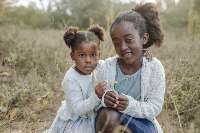 Portrait of sisters crouching on field at park