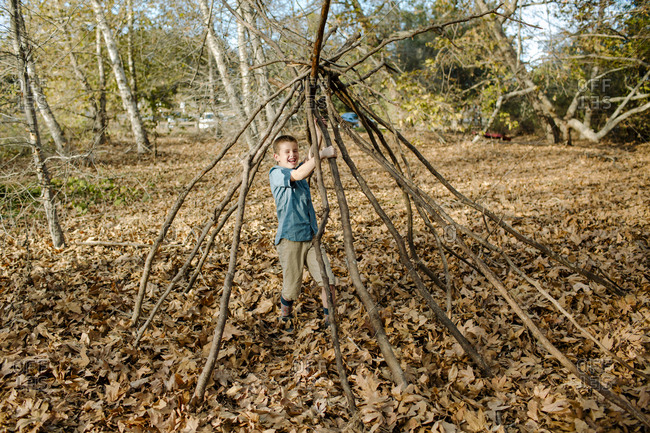 Cheerful boy standing amidst sticks arranged on field at park during autumn