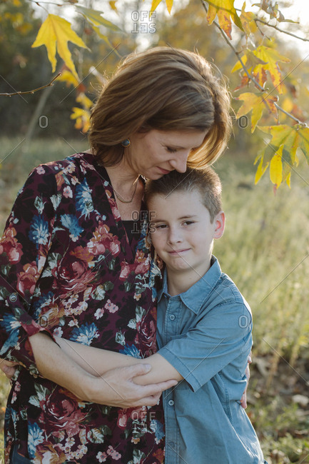 Son embracing mother while standing on field at park