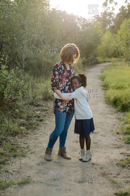 Full length portrait of girl embracing mother while standing on trail amidst field at park