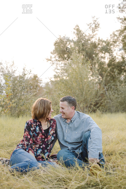 Smiling couple sitting on field at park