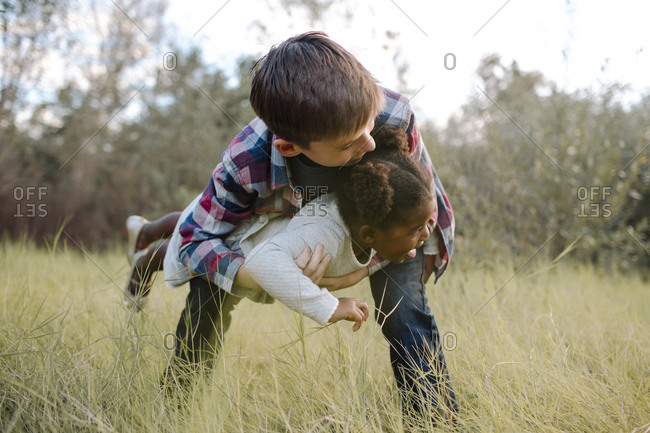 Boy carrying sister while playing on field at park