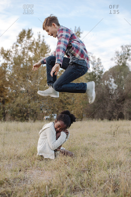 Side view of boy jumping over girl crouching on field at park