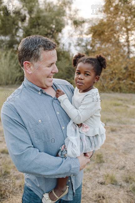 Portrait of girl with father standing on field at park