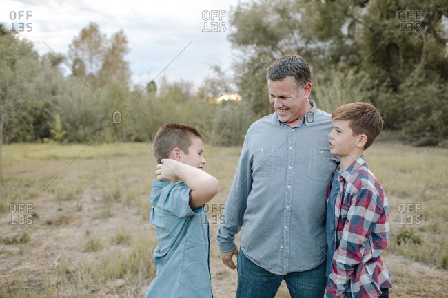 Father talking to sons while standing on field at park