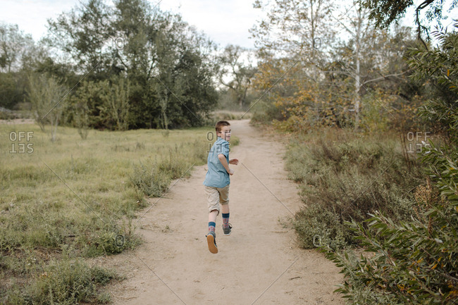 Rear view of boy running on trail amidst plants at park