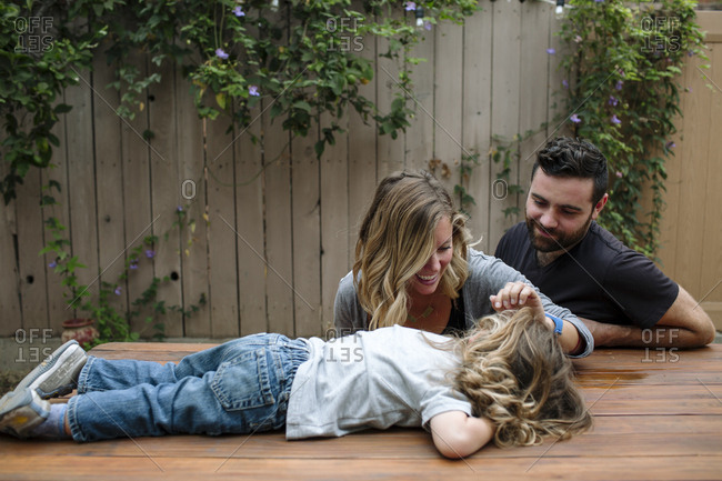Parents playing with daughter lying on table at backyard