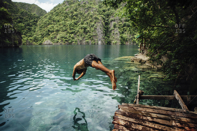 Full length of shirtless man diving into sea against mountains