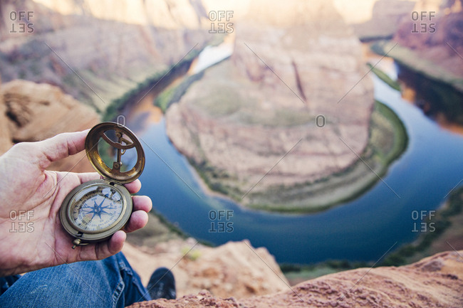 Low section of man holding navigational compass against Horseshoe Bend