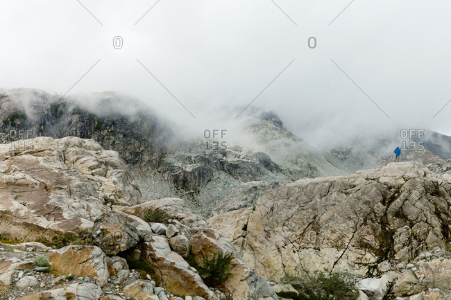 Mid distance view of hiker standing on mountain during foggy weather