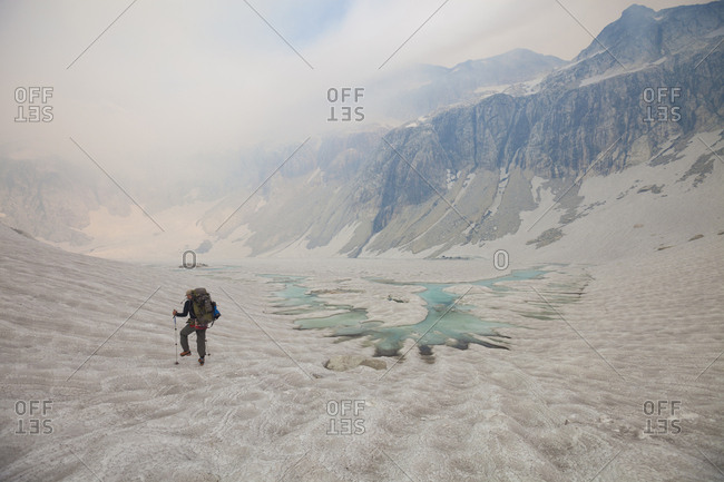 Rear view of hiker walking on glacier against sky