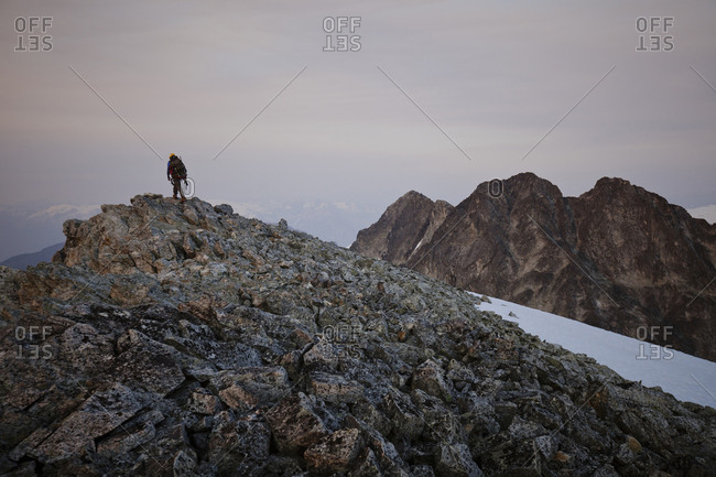Rear view of hiker on cliff against sky