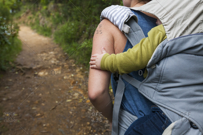 Rear view of mother carrying son in baby carriage while walking in forest
