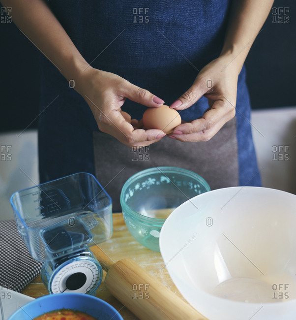Midsection of woman breaking egg in bowl at kitchen