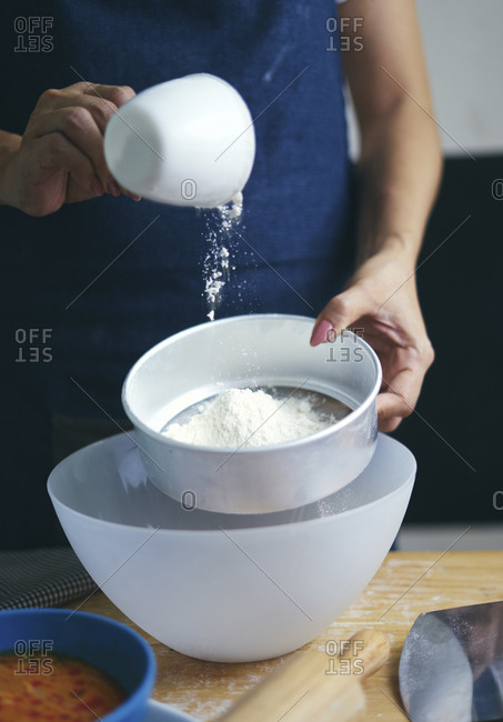 Midsection of woman sifting flour in bowl at kitchen