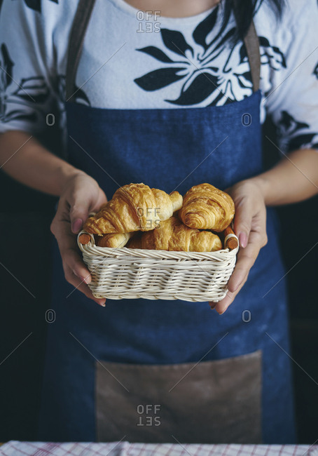 Midsection of woman holding croissants in basket at kitchen