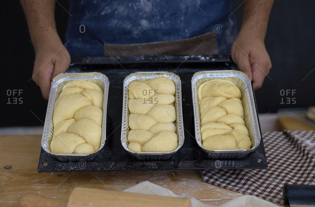 Midsection of man holding breads in containers on baking sheet while standing in bakery