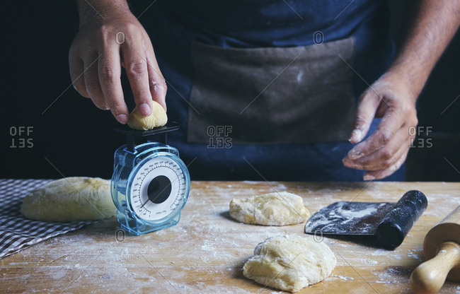 Midsection of man weighing dough while preparing food at table in bakery