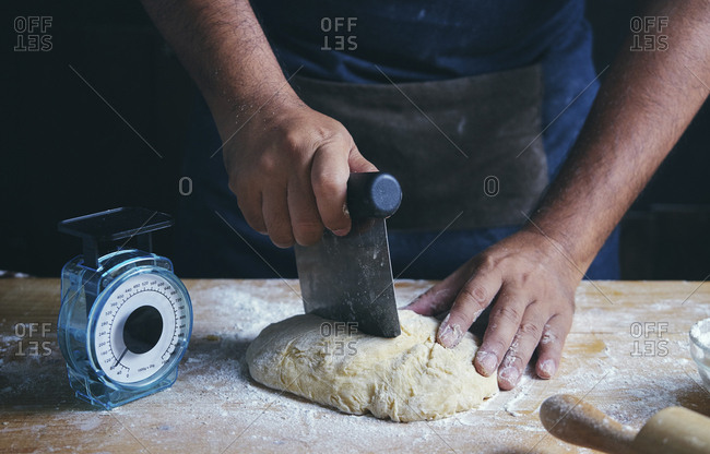 Midsection of man cutting dough at table in bakery