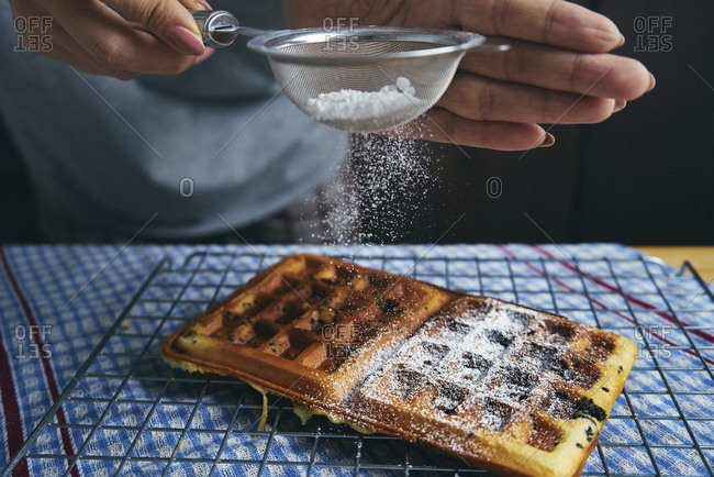 Midsection of woman sprinkling powdered sugar on waffle at table