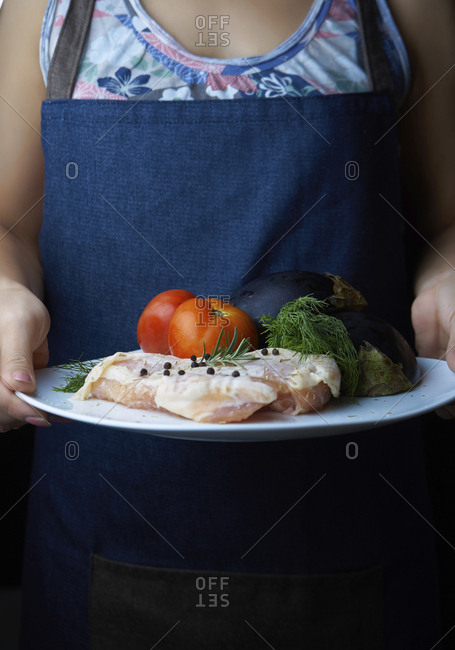 Midsection of woman holding chicken meat with vegetables in plate