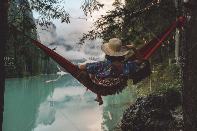 Young woman looking at view while sitting in hammock over lake