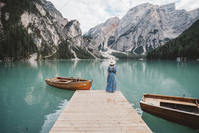 Rear view of young woman standing on pier over lake against mountains