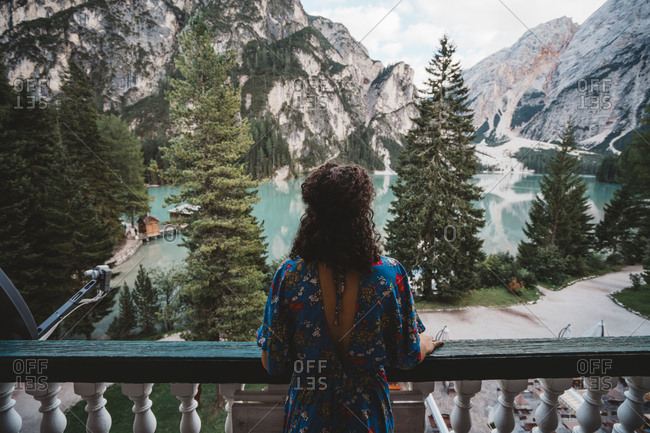 Young woman looking at view while standing in balcony against mountains and lake