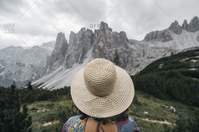 Rear view of female hiker wearing hat standing on mountain against cloudy sky