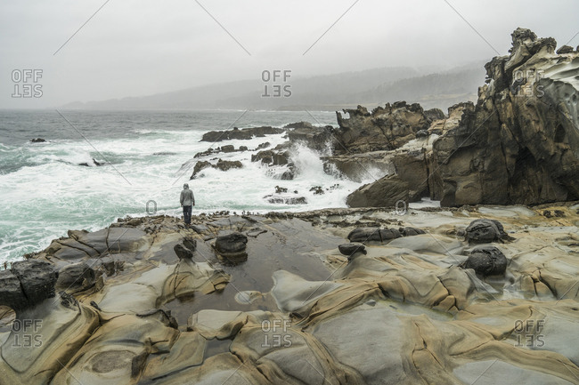 High angle view of man standing on rocks at beach against sky during foggy weather