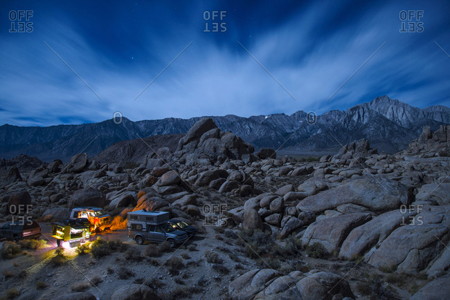 High angle view of vehicles by campfire against sky at night