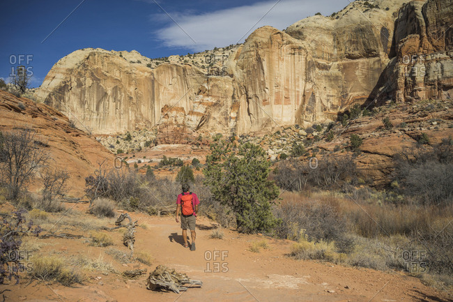 Rear view of hiker with backpack walking on desert against rock formations