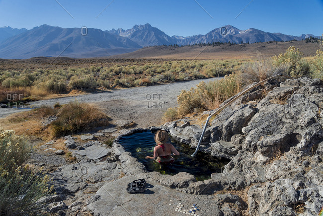 High angle view of woman in pond by rock formations against mountains
