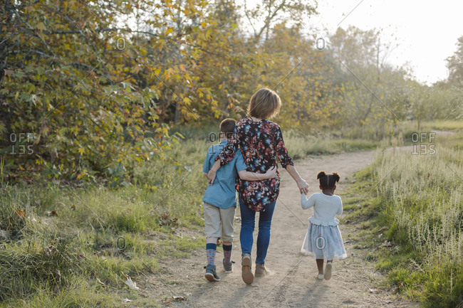 Rear view of woman with daughter and son walking on trail amidst field at park