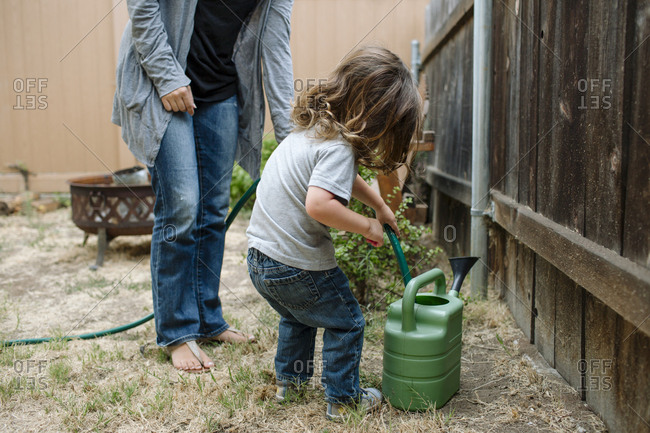 Full length of daughter using garden hose to fill watering can while standing by mother at backyard