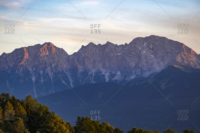 Low angle view of mountains against cloudy sky during sunset