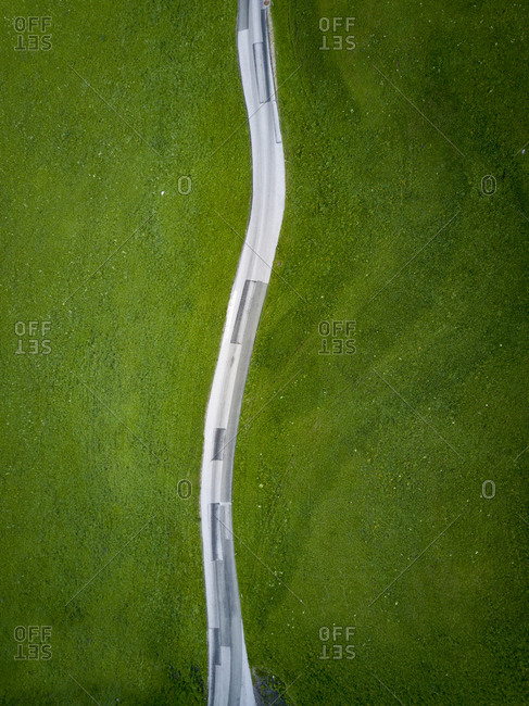 High angle view of road amidst grassy field