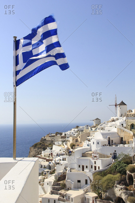 Greek Flag waving by sea against town and clear sky