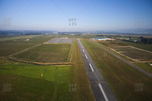 Aerial view of runway amidst field against sky