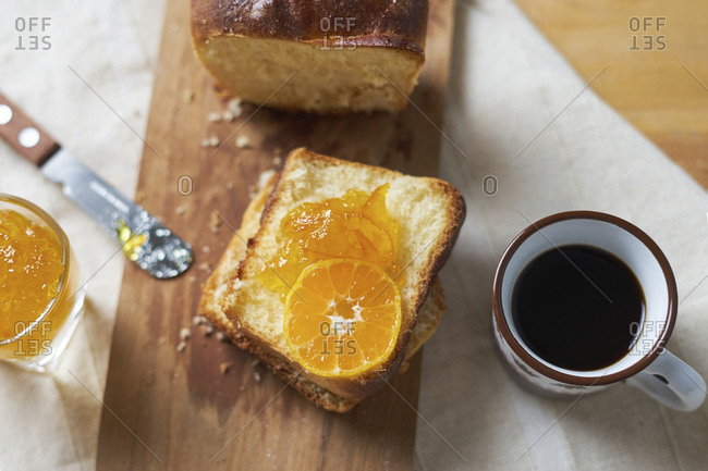 High angle view of bread and jam on cutting board by black coffee