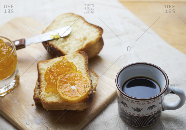 Close-up of bread and jam on cutting board by black coffee