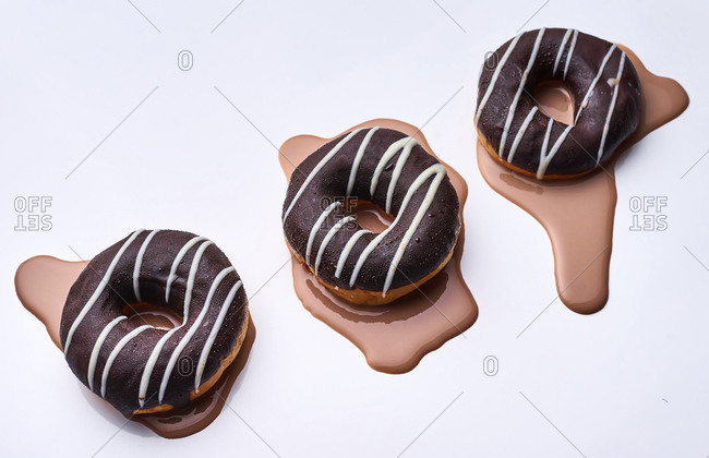 High angle view of chocolate donuts on white background