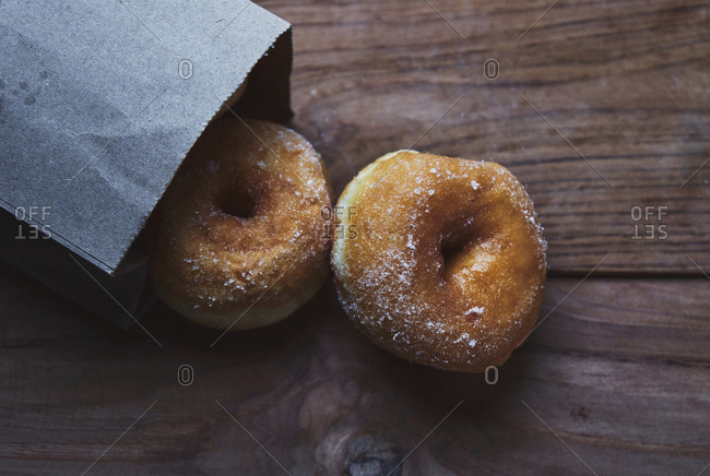 High angle view of donuts by paper bag on table