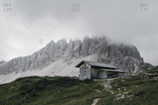 Scenic view of house on hill by mountain against cloudy sky during foggy weather