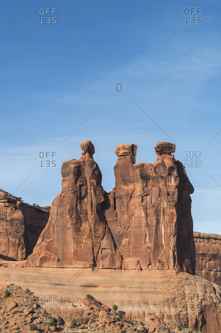 Low angle view of rock formations at Arches National Park against blue sky
