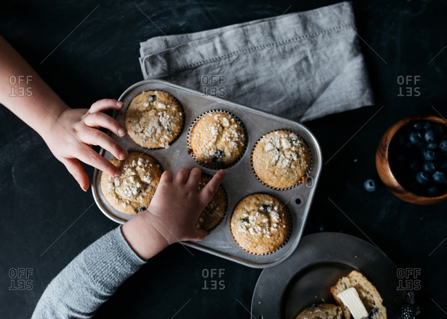 Two children grabbing blueberry muffins from pan