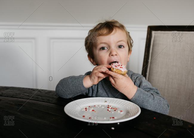 Little boy eating Valentine's cupcake