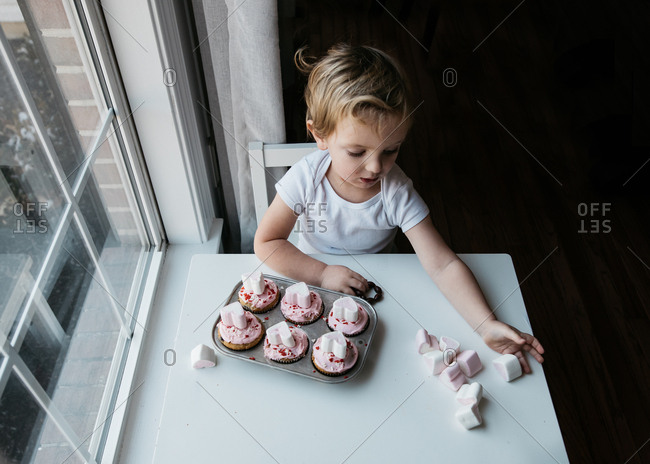 Little boy sitting at table with Valentine's cupcakes