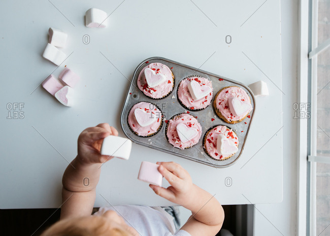 Little boy sitting eating marshmallows and Valentine's cupcakes