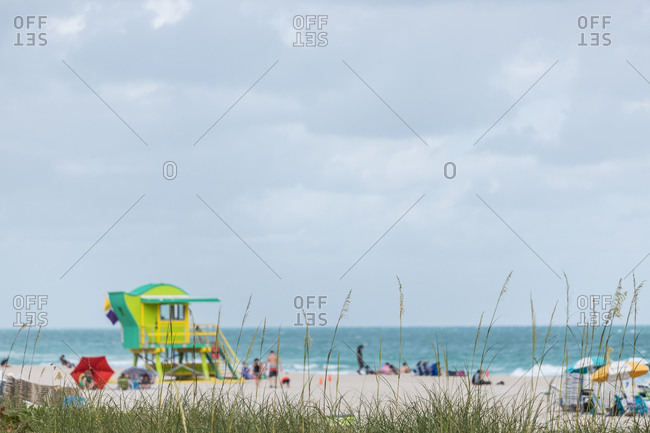 Miami, Florida - January 15, 2018: Beachgoers on beach by life guard station designed by architect William Lane